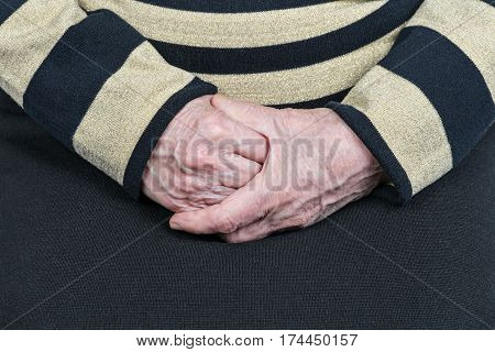Wrinkled hands of the old woman sitting holding one after the other, close-up