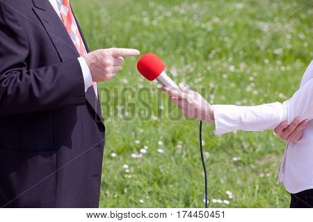 Female reporter making media interview with business person or politician