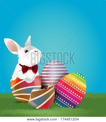 Little white bunny worn red bow in easter egg shell and two easter eggs on green grassland.