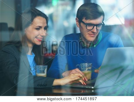 Beautiful young woman and man negotiating in a cafe - modern business concept
