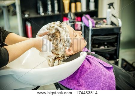 Hairdresser washing customer young woman meches head with professional shampoo and hair conditioner - People beauty care concept - Focus on head washed - Warm filter soft vignette