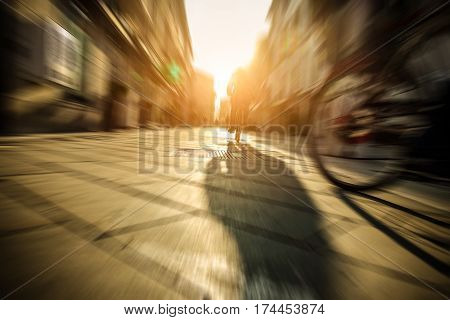 Citizen speeding with old style italian bicycle on city cente - People on town streets - Metropolis lifestyle concept - Radial blur composition with focus on middle woman driving bike - Warm filter