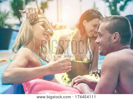Happy friends toasting cocktails in swimming pool party - Young people chilling on summer vacation in aqua park - Holidays concept - Focus on right man - Matte warm filter with soft vignette