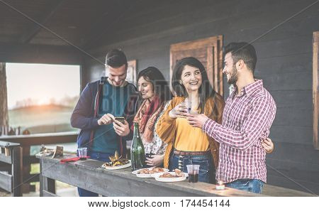Happy young couples toasting red wine and eating barbecue in backyard wooden house - Cheerful people having fun at sunset in summer time - Focus on right man face - Warm contrast filter