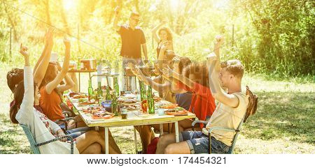 Happy friends having fun eating at barbecue party outdoor big house backyard garden - Young diverse culture people enjoying bbq lunch - Friendship and grill concept - Warm filter - Focus on right man