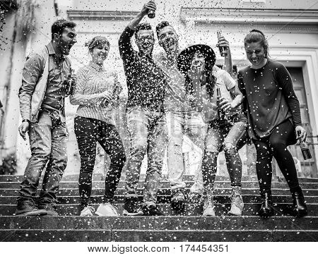 Group of friends making party outdoor with confetti and beers - Young people drinking alcohol and having fun on the street - Black and white editing - Friendship concept - Warm contrast filter