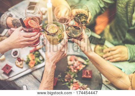 Group of friends enjoying appetizer in american bar - Young people hands cheering with wine and tropical fruits cocktails - Radial purple and green filters editing - Focus on left hand glass