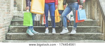 Young women with gift bags doing shopping - Casual girls on stair case after buying clothes and female accessories in city shops center - Sales concept - Focus on bags - Warm cinematic filter