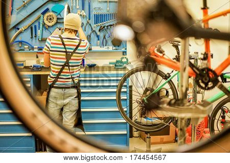 Owner bike mechanic preparing racing bicycles in workshop - Young trendy man checking new carbon fiber superbike indoor - Professional maintenance concept - Focus on guy - Warm filter