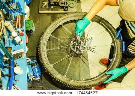 Top view of stylish bicycle mechanic working in mountain bike shop - Young man checking wheel spoke superbike on workbench - Repairing job concept - Focus on right hand - Warm filter