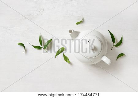 Tea concept teapot with tea surrounded with green tea leaves view from above