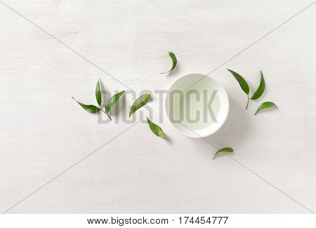 Tea concept white cup with tea surrounded with green tea leaves view from above