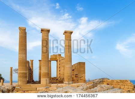 Ancient Greek pillars at the Lindos acropolis with blue cloudy sky in the background