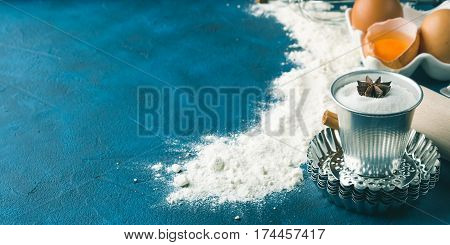 Baking tools rolling pin, sifter, letter moulds. Sweet food cake cookie dough ingredients on dark blue background. Banner copy space frame