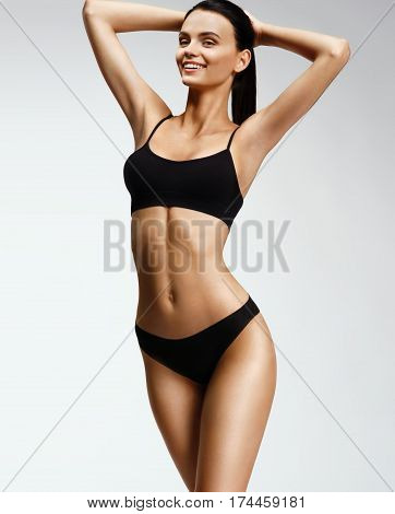 Laughing sporty girl in black bikini posing on grey background. Photo of attractive girl with slim toned body. Beauty and body care concept