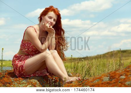 sexy redhead woman in a dress outdoors. Beautiful stylish romantic young girl on nature background