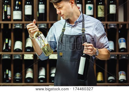 Sommelier choosing between two bottles of red and white wine on background of shelves with elite drink in cellar. Professional expert in winemaking in apron
