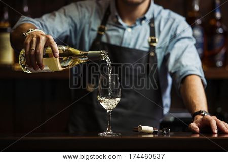 Male sommelier pouring white wine into long-stemmed wineglasses. Waiter with bottle of alcohol beverage. Bartender at bar counter pour elite drink into long-stemmed glass