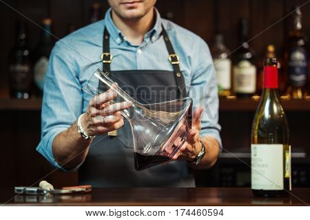 Wineglass at bar counter at background of sommelier with decanter with wine. Glass carafe mixing bowl at the hands of waiter. Bartender at workplace