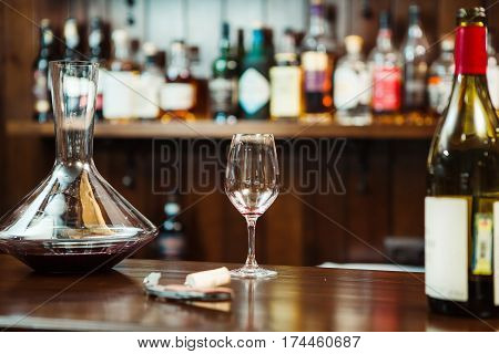 Decanter with red wine and a glass on the bar