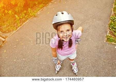 Little girl in helmet and roller skates at a park. child outdoors