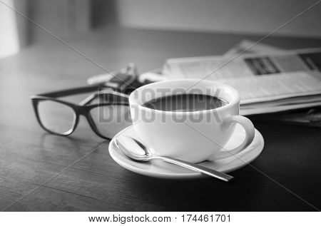 Newspaper reading glasses black and white coffee cup and mobile phone on business desk business newspaper background concept.