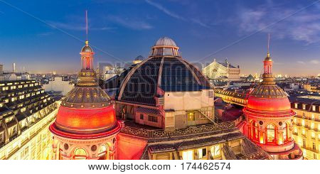 Aerial panoramic view of Opera Garnier, Neo-Renaissance Printemps gallery dome at night, Paris, France