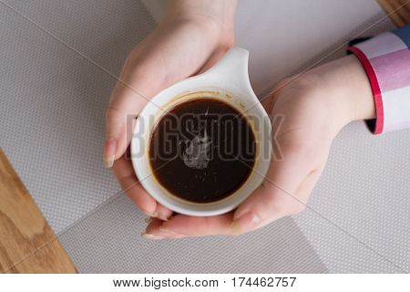 hands hugging a Cup of strong fresh coffee on the table
