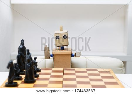 robot with hands sitting at the table playing a game of chess. Artificial Intelligence