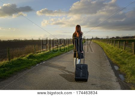 runaway girl standing with her suitcase on the road and look for the last time to her native village