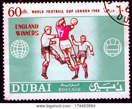 DUBAI - CIRCA 1966: Postage stamp printed in Dubai  with a picture of a football players, with the inscription