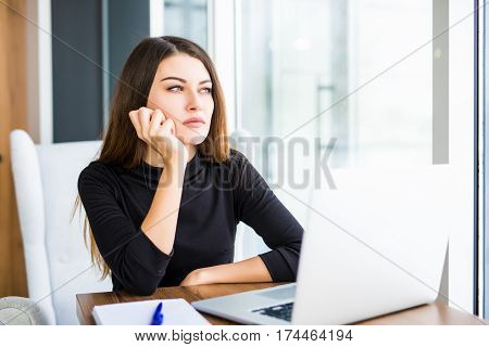 Bored young woman in the office working with a laptop and staring at computer screen