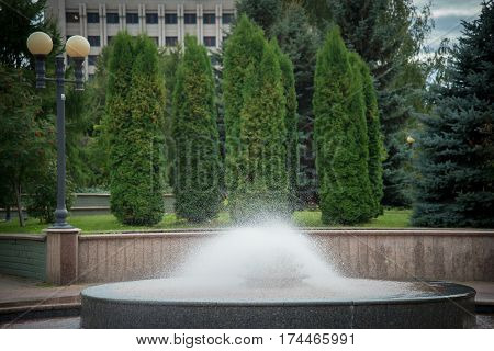 A semicircular fountain in the park with spray on a background of green trees