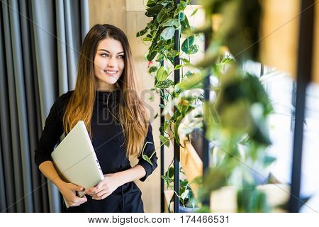 Portrait Of Successful Smiling Businesswoman Holding Laptop Computer In Her Hands. Happy Beautiful Confident Woman Standing At Office Wall With Notebook. Business People.