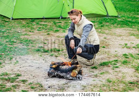 traveler stoking campfire, dressed in trekking clothes sitting beside a campfire. Enjoying outdoor recreation, camping holiday .