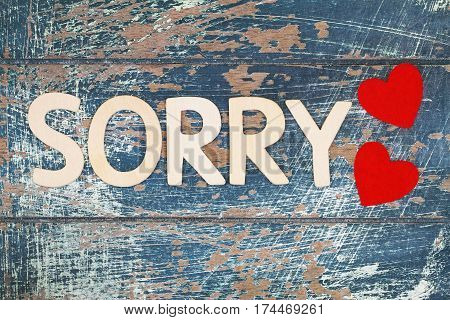 Sorry written with wooden letters and two red hearts on rustic surface