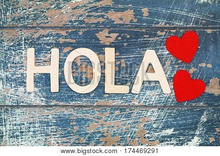 Hola (which means Hello in Spanish) written with wooden letters on rustic surface and two red hearts