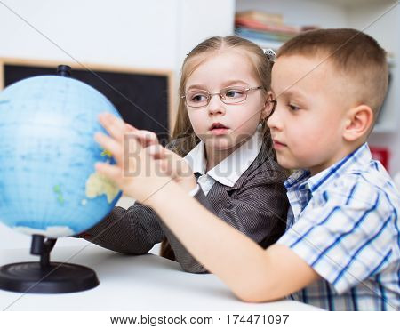 closeup portrait of  schoolchildren are examining globe