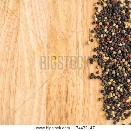 Multicolored Peppercorns On Wooden Background. Dry Peper Mix