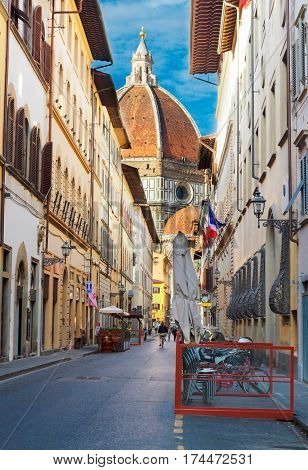 street in historical town with view of historic cathedral dome, Florence, Italy
