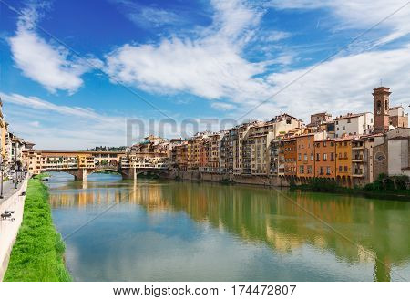 Ponte Santa Trinita bridge and Ponte Vecchio bridge with medieval houses over the water of Arno River, Florence, Italy