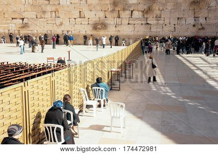 Worshipers pray at the Wailing Wall. The most holy site in Jerusalem, Israel - Western Wall with people sitting and staying near the Wall to pray