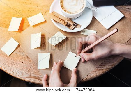 Close up of woman hands writing love notes stickers by wooden pencil. Young beautiful woman drawing love message for a boy friend in a cafe. View from above.
