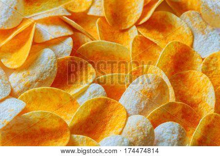 Potato chips on a wooden billet. Rippled fresh organic potato chips background.