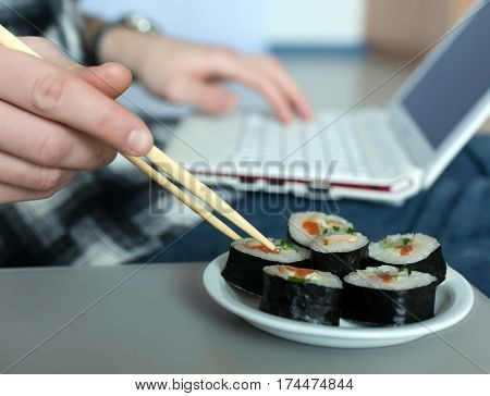 Asian Sushi Set and Man working on Laptop Computer taking Food with wooden Chopsticks