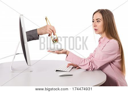 Internet Food ordering and instant Delivery young Woman makes Order at Computer Hand of Agent appears from Screen instantly delivering Order holding Sushi Roll wooden Chopsticks on white Background.