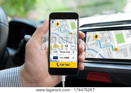 man hand in car holding phone with application call taxi on screen