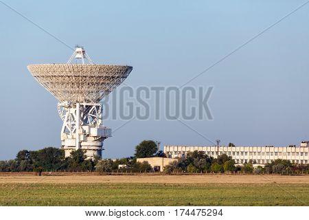 huge white satellite antenna radio telescope on the background of sky