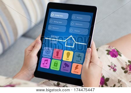 woman on sofa in flowered dress holding tablet computer with app smart home