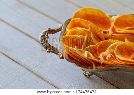 Potato chips in bowl and fresh potato fresh organic potato chips